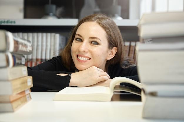 Młoda kobieta siedzi w bibliotece