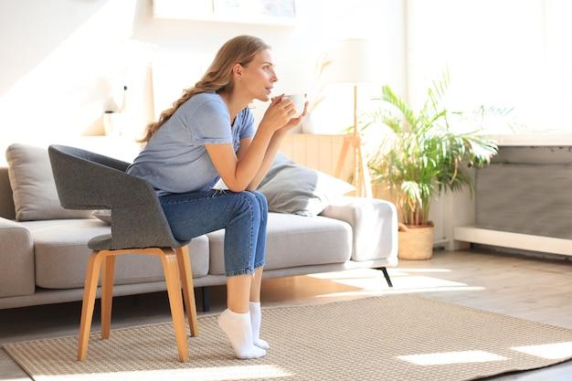 Młoda kobieta siedzi w fotelu i pije kawę.