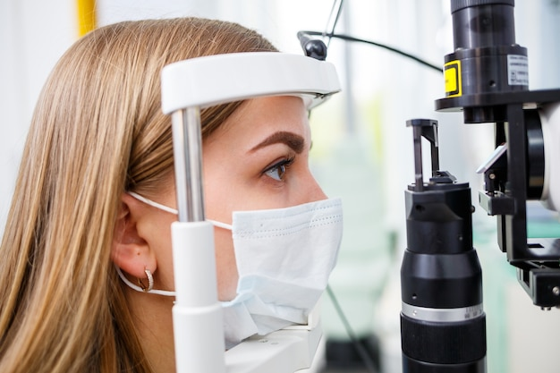 Młoda kobieta siedzi w fotelu, patrząc na lampę szczelinową podczas badania lekarskiego w oczy