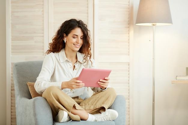 Młoda kobieta siedzi w fotelu w salonie i wykonuje swoją pracę przy użyciu komputera typu tablet i internetu