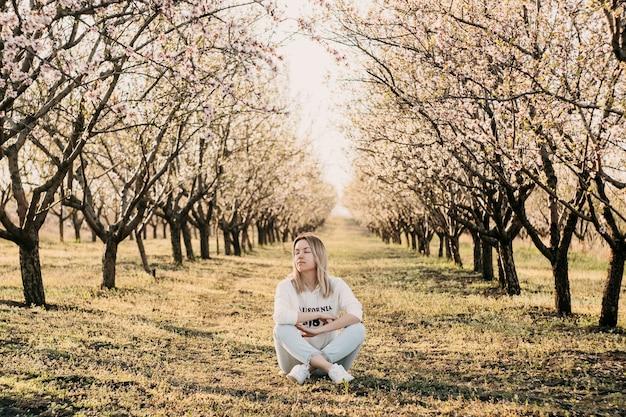 Młoda kobieta siedzi w ogrodzie z drzewami w rozkwicie