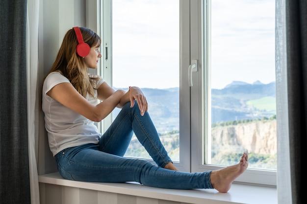 Młoda kobieta siedzi w oknie swojego domu, słuchając muzyki w słuchawkach. pojęcie nowych technologii.