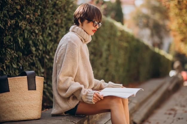 Młoda kobieta siedzi w parku i czyta