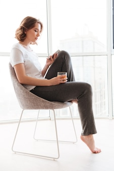 Młoda kobieta siedzi w pobliżu okna rozmowy przez telefon.