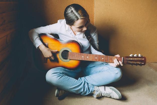 Młoda kobieta siedzi w pokoju na podłodze i gra na gitarze w domu.