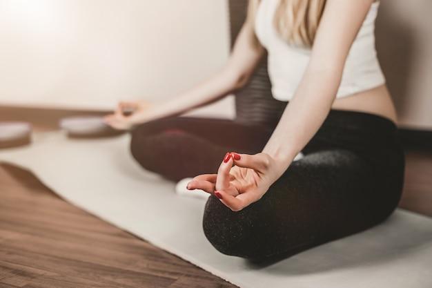 Młoda kobieta siedzi w pozycji lotosu i medytacji w domu podczas kwarantanny. zdrowy tryb życia, rekultywacja