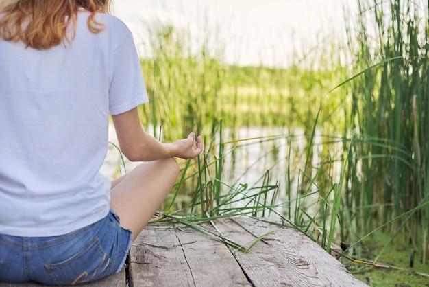 Młoda kobieta siedzi w pozycji lotosu na moście w pobliżu wody