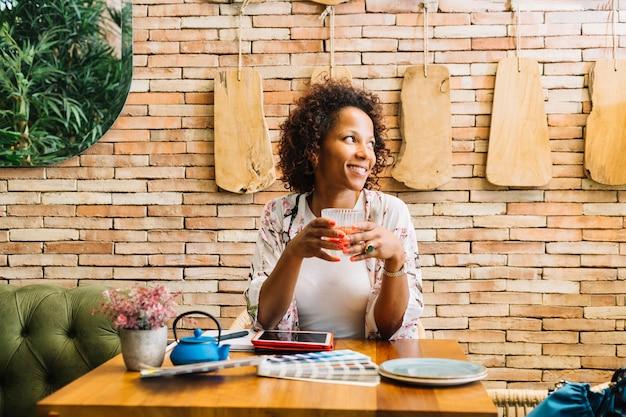 Młoda kobieta siedzi w restauracji trzymając szklankę soku