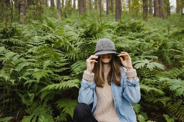 Młoda kobieta siedzi w wysokiej trawie