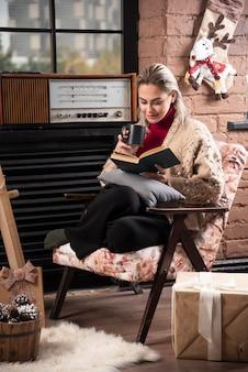 Młoda kobieta siedzi z książką i pije kawę