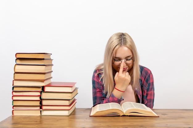 Młoda kobieta siedzi z książkami i czyta na białym tle