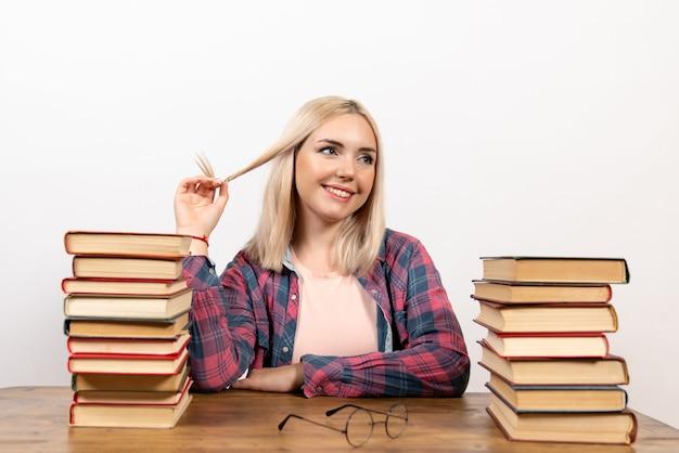 Młoda kobieta siedzi z książkami na białym tle
