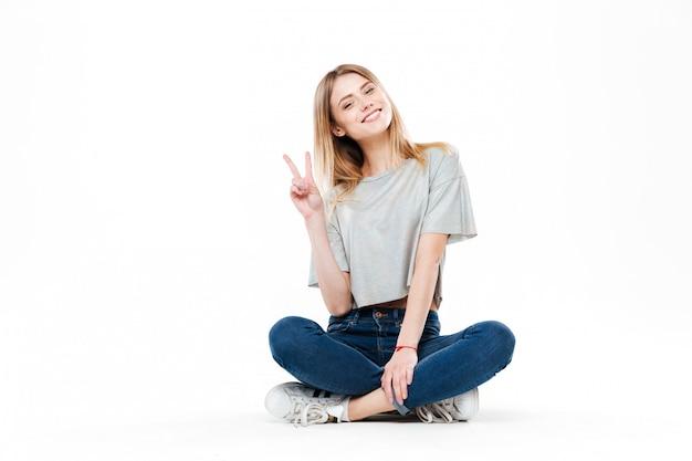 Młoda kobieta siedzi ze skrzyżowanymi nogami na białym tle