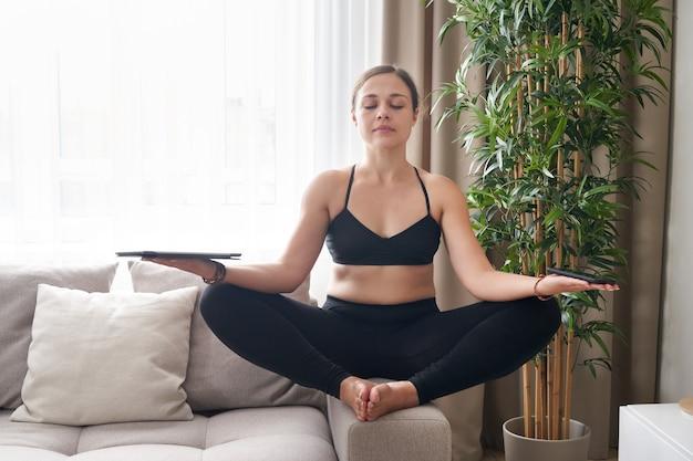 Młoda kobieta siedzi ze skrzyżowanymi nogami na kanapie w pozycji lotosu, medytując w domu w salonie
