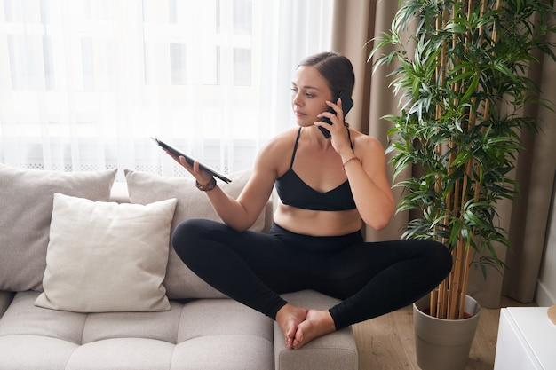 Młoda kobieta siedzi ze skrzyżowanymi nogami na kanapie w pozycji lotosu, używając tabletu i telefonu w domu w salonie