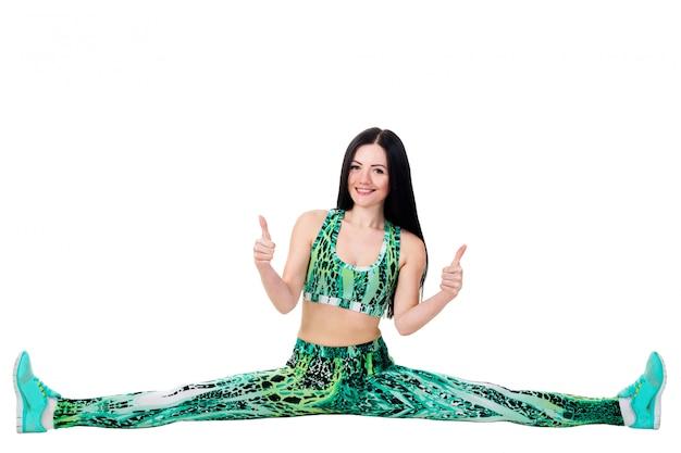 Młoda kobieta siedzieć na sznurku i rozciąganie, pokazując palcami w górę, znak ok.