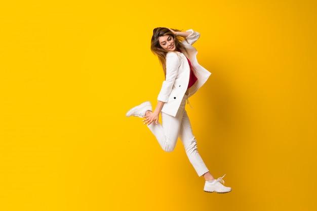 Młoda kobieta skacze nad odosobnioną kolor żółty ścianą