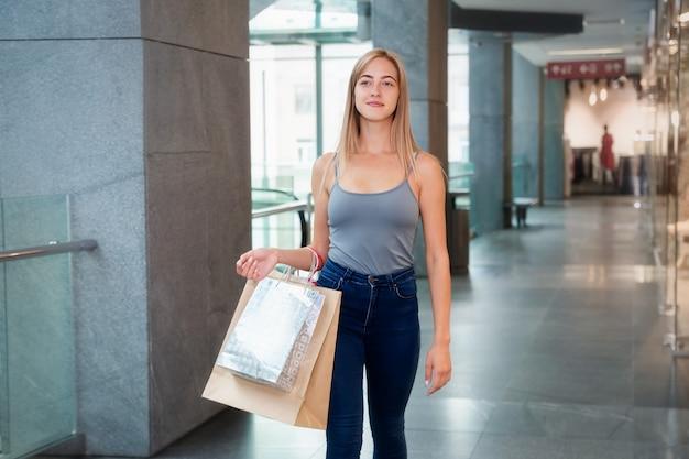 Młoda kobieta skacze w centrum handlowym trzyma torby na zakupy w ręce i spacery
