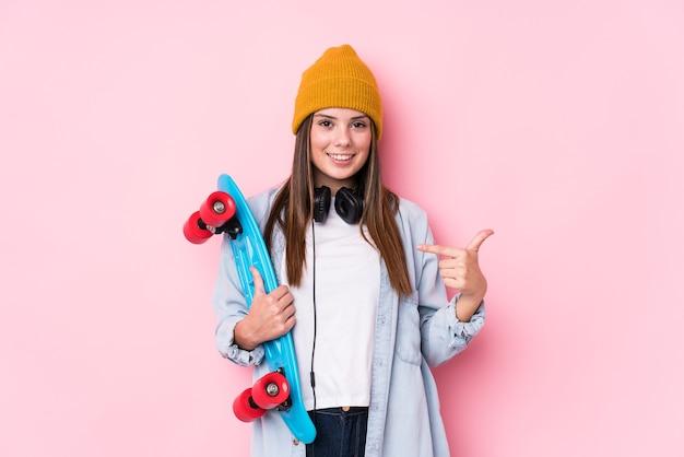 Młoda kobieta skater gospodarstwa skate osoba, wskazując ręką na przestrzeń kopii koszuli, dumna i pewna siebie