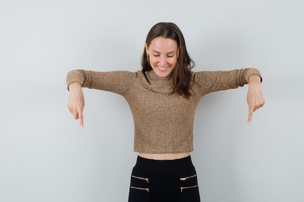 Młoda kobieta skierowana w dół w bluzkę, spódnicę i zadowolony wyglądający. przedni widok.
