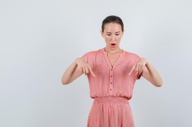 Młoda kobieta skierowana w dół w pasiastej sukience i patrząc zaciekawiony. przedni widok.