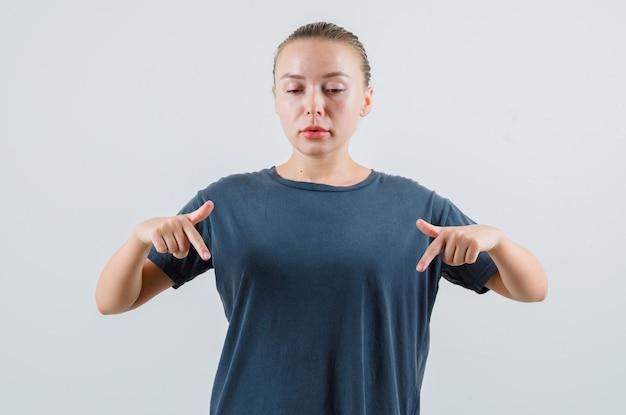 Młoda kobieta skierowana w dół w szarej koszulce i patrząc skoncentrowany