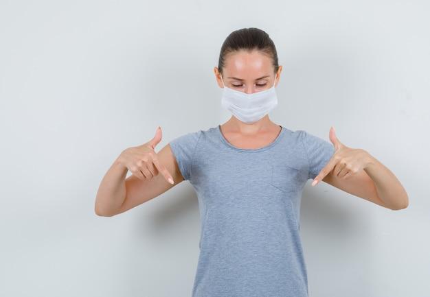 Młoda kobieta skierowana w dół w szary t-shirt, maska i patrząc skoncentrowany. przedni widok.