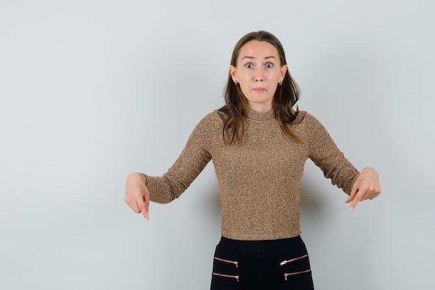 Młoda kobieta skierowana w dół w złotej bluzce i patrząc zaskoczony, widok z przodu.