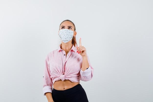 Młoda kobieta skierowana w górę w koszuli, spodniach, masce medycznej i wygląda pewnie. przedni widok.