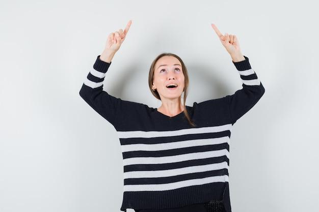 Młoda kobieta skierowana w górę z palcami wskazującymi w pasiastej dzianinie i czarnych spodniach i wygląda na zaskoczoną