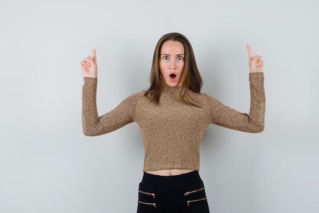 Młoda kobieta skierowana w górę z palcami wskazującymi w pozłacanym swetrze i czarnych spodniach i wygląda na zaskoczoną