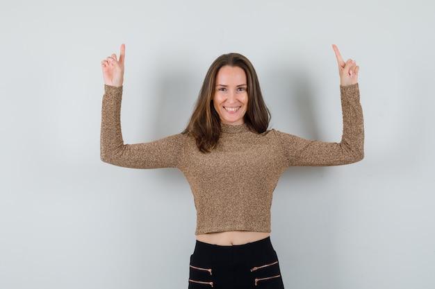 Młoda kobieta skierowana w górę z palcami wskazującymi w złoconym swetrze i czarnych spodniach i wygląda na szczęśliwą