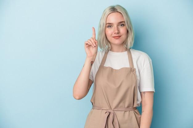 Młoda kobieta sklep kaukaski sprzedawca na białym tle na niebieskim tle wyświetlono numer jeden palcem.