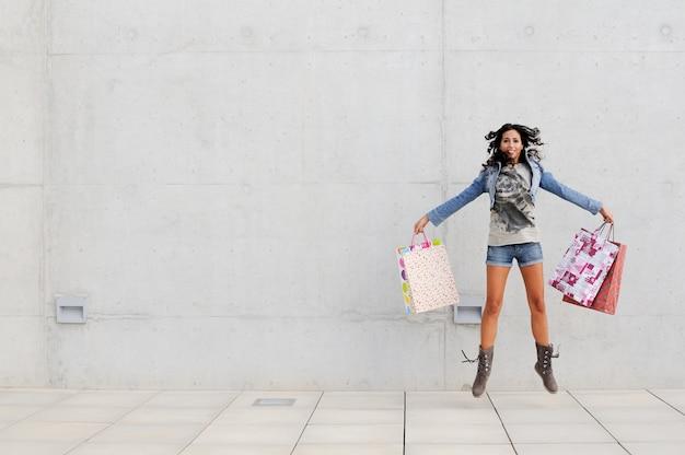 Młoda kobieta skoki z torby na zakupy