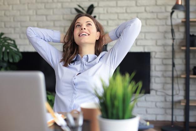 Młoda kobieta skrzyżowane ręce za głową, ciesząc się przerwą w domu. spokojna beztroska biznesowa kobieta odpoczywa przy stole z komputerem, odwracając wzrok, marząc o przyszłości.