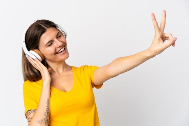 Młoda kobieta słowacki na białym tle słuchania muzyki i śpiewu