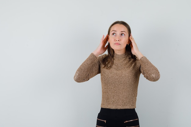 Młoda kobieta słucha czegoś, odwracając wzrok w złotej bluzce i patrząc uważnie, widok z przodu. miejsce na tekst