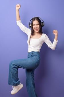 Młoda kobieta słucha muzyka na purpurowym tle