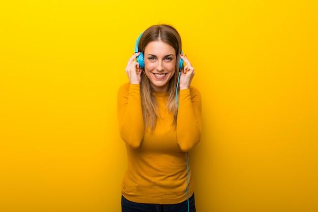 Młoda kobieta słucha muzyka z hełmofonami na żółtym tle