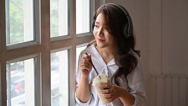 Młoda kobieta słucha muzyki i cieszy się piosenki