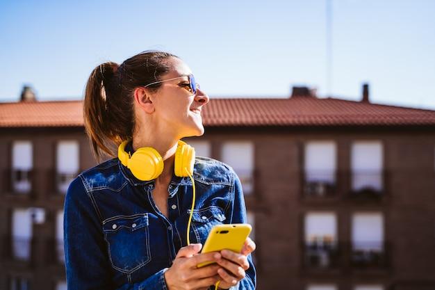 Młoda kobieta słucha muzyki na telefonie komórkowym i żółtej słuchawki. zabawa i styl życia