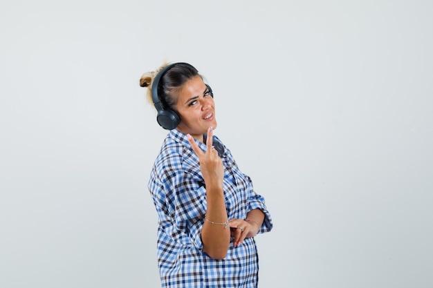 Młoda kobieta słucha muzyki przez słuchawki, pokazując znak v w kraciastej koszuli i patrząc wesoło. .