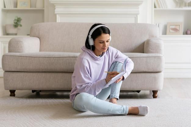 Młoda kobieta słucha muzyki w domu