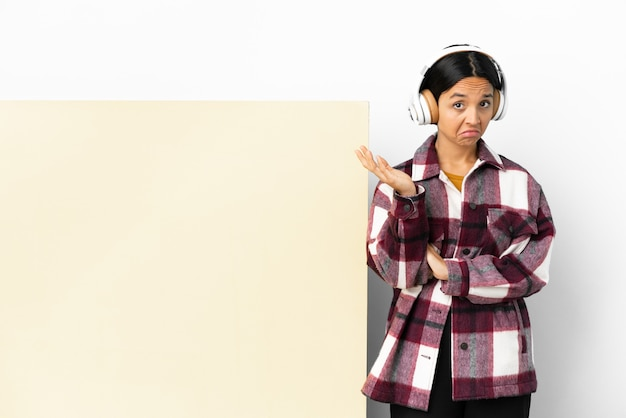 Młoda kobieta słucha muzyki z dużą pustą tabliczką na białym tle, robiąc gest wątpliwości