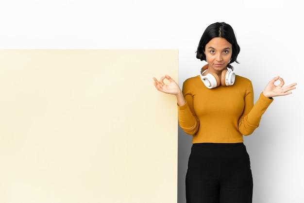 Młoda kobieta słucha muzyki z dużym pustym plakatem na białym tle w pozie zen