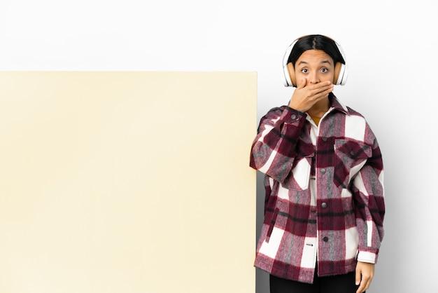 Młoda kobieta słucha muzyki z dużym pustym plakatem na białym tle zakrywającym usta ręką