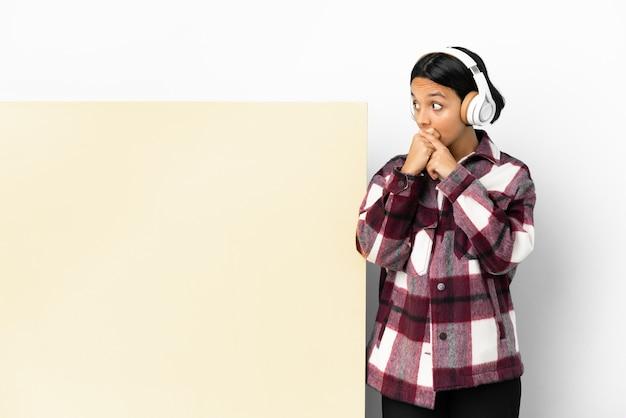 Młoda kobieta słucha muzyki z dużym pustym plakatem na izolowanej ścianie zakrywającej usta i patrząc w bok