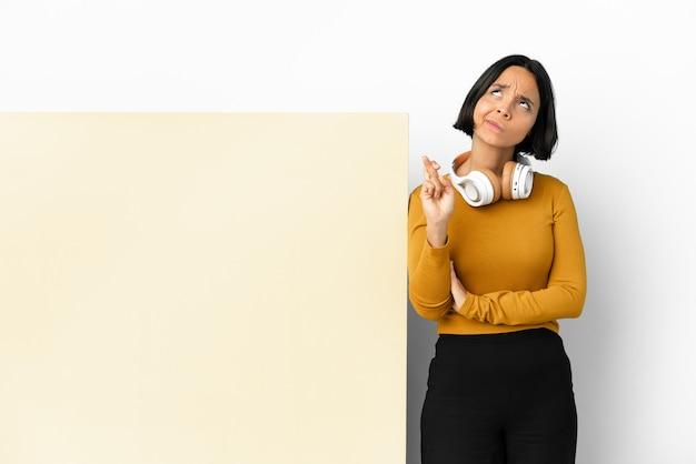 Młoda kobieta słucha muzyki z dużym pustym plakatem na odizolowanej ścianie z krzyżującymi palcami i życząc wszystkiego najlepszego