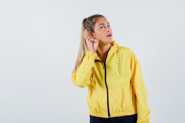 Młoda kobieta słucha w żółtym płaszczu i patrząc skoncentrowany