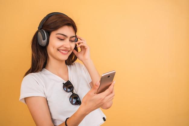 Młoda kobieta słuchania muzyki i korzystania ze smartfona.